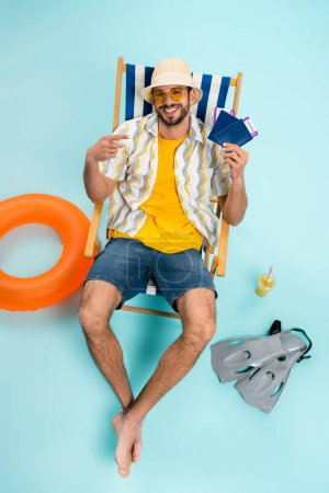 High angle view of smiling man pointing at passports near swimming flippers, orange juice and inflatable ring on blue background