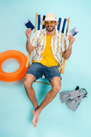 Photo for High angle view of smiling man in sunglasses holding passports near swimming flippers and inflatable ring on blue background - Royalty Free Image
