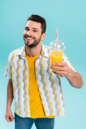 Smiling man holding blurred orange juice in plastic cup isolated on blue