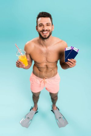 High angle view of positive shirtless man holding orange juice and passports on blue background