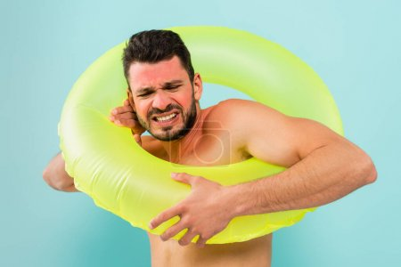 Photo for Stressed man with sunburn wearing inflatable ring isolated on blue - Royalty Free Image