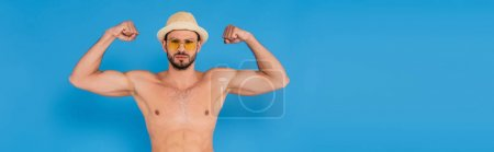 Photo pour Homme torse nu en chapeau de soleil montrant les muscles sur fond bleu, bannière - image libre de droit