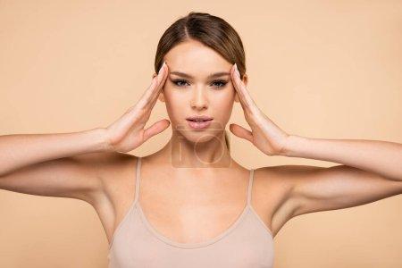 junge Frau blickt in die Kamera, während sie die Hände in Gesichtsnähe hält, isoliert auf beige