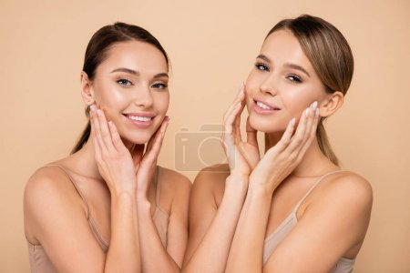 smiling women with perfect skin touching faces isolated on beige