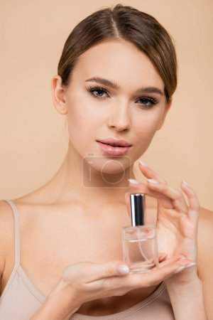 pretty woman with natural makeup holding perfume isolated on beige