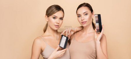 young women with natural visage holding eye shadows and highlighter palettes isolated on beige, banner