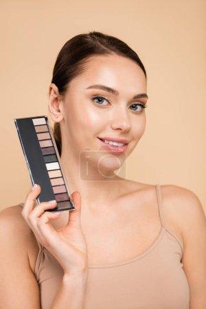 Photo pour Femme heureuse avec palette d'ombres à paupières souriant à la caméra isolée sur beige - image libre de droit