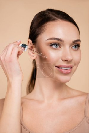 Photo for Smiling woman dropping cosmetic serum on face isolated on beige - Royalty Free Image