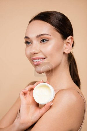 Photo for Pleased woman holding container with cosmetic cream isolated on beige - Royalty Free Image