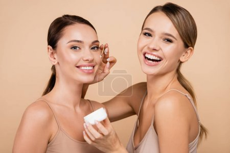 laughing woman applying face cream on smiling friend isolated on beige