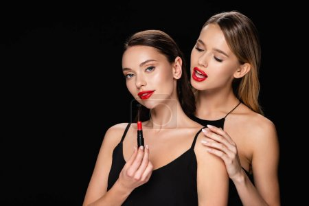 sinnliche Frau berührt Schulter einer hübschen Freundin mit rotem Lippenstift isoliert auf schwarz