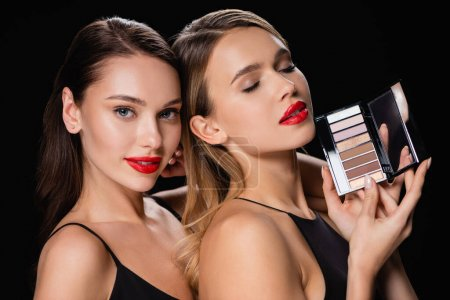Photo pour Sensual woman looking at camera near pretty friend with eye shadows palette isolated on black - image libre de droit