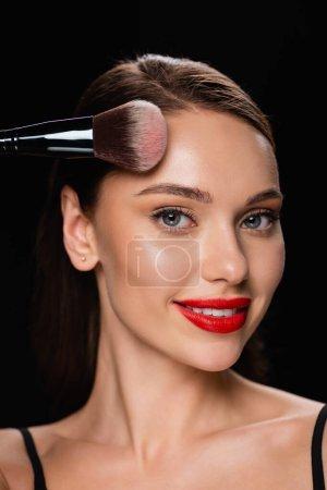 lächelnde Frau, die in die Kamera schaut, während sie die Stirn auf Schwarz pudert