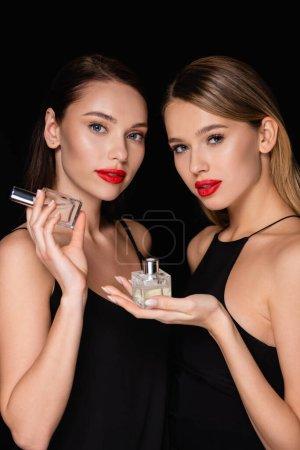 mujeres encantadoras mirando a la cámara mientras sostiene perfumes aislados en negro