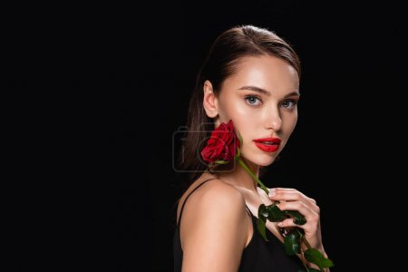Photo pour Pretty woman with red lips and rose looking at camera isolated on black - image libre de droit