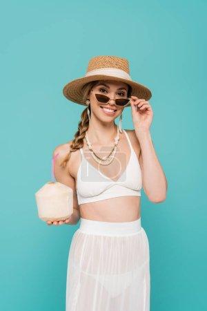 Photo pour Femme positive en chapeau de soleil et maillot de bain tenant cocktail en noix de coco isolé sur bleu - image libre de droit