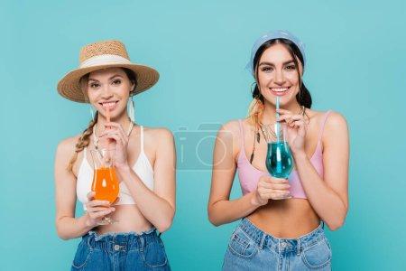 Photo pour Jolies femmes avec des cocktails regardant la caméra isolée sur bleu - image libre de droit