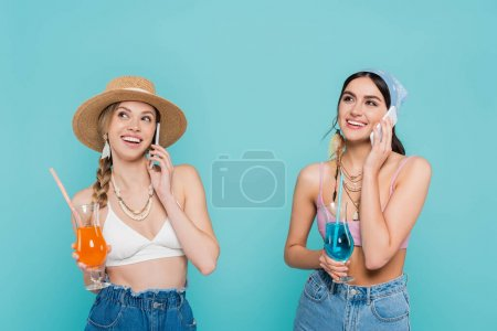 Happy women in tops holding cocktails and talking on smartphones isolated on blue