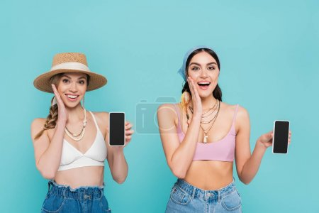 Positive women in tops holding smartphones isolated on blue