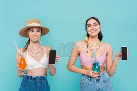 Photo pour Femmes souriantes en hauts et colliers tenant smartphones et cocktails isolés sur bleu - image libre de droit