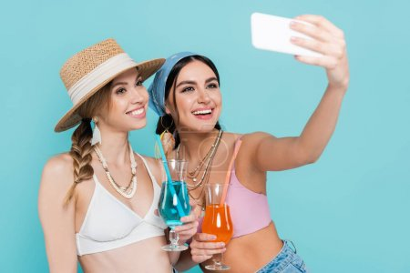 Smiling friends in tops holding cocktails and taking selfie on smartphone isolated on blue