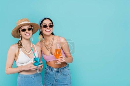 Photo pour Des femmes souriantes portant des lunettes de soleil tenant des cocktails isolés sur bleu - image libre de droit