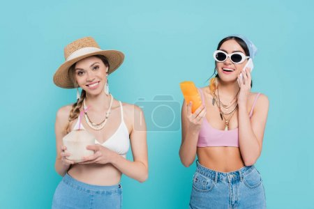 Photo for Smiling woman holding cocktail in coconut near friend with sunscreen talking on smartphone isolated on blue - Royalty Free Image