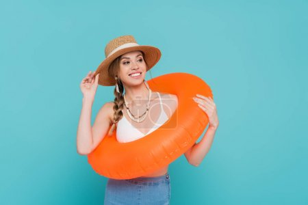 Smiling woman in straw hat holding swim ring isolated on blue