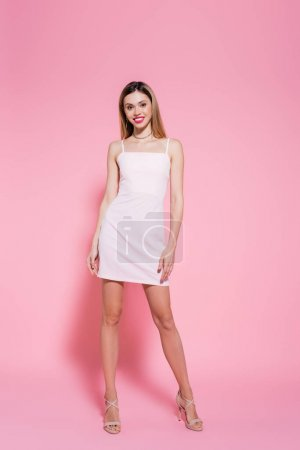 Photo for Smiling woman in dress looking at camera on pink background - Royalty Free Image
