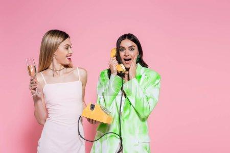 Femme excitée parlant au téléphone ami proche avec du champagne sur fond rose