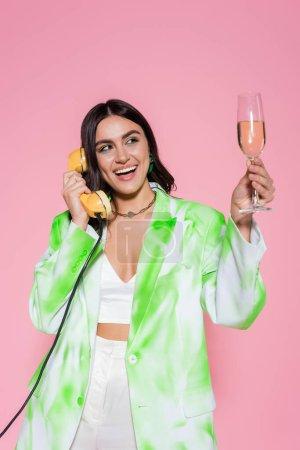 Photo pour Jolie femme parlant au téléphone et tenant une coupe de champagne isolée sur rose - image libre de droit