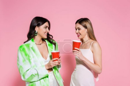 Young friends holding plastic cups on pink background
