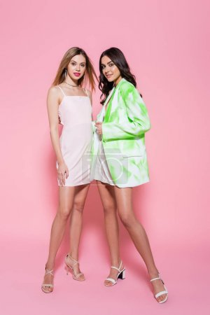 Pretty women in stylish clothes smiling at camera on pink background