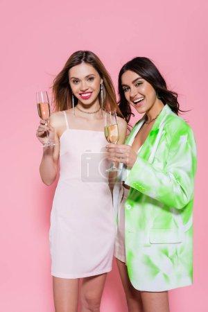 Photo pour Jeunes femmes dans des vêtements élégants tenant champagne sur fond rose - image libre de droit