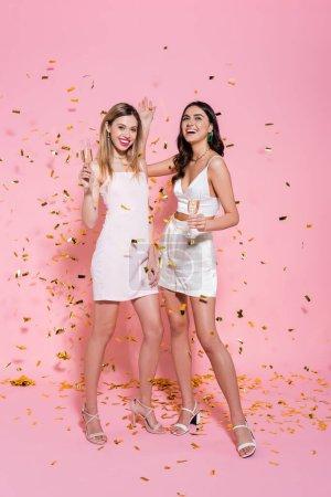 Photo pour Jolies femmes tenant du champagne sous des confettis dorés sur fond rose - image libre de droit
