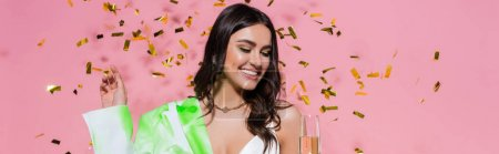 Pretty woman smiling while looking at glass of champagne near confetti on pink background, banner