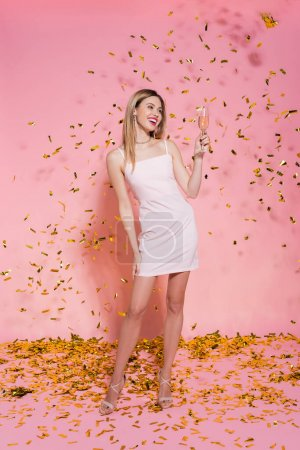 Pretty woman in dress holding champagne under golden confetti on pink background