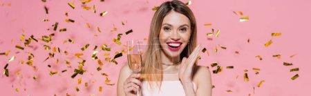 Mujer positiva mirando a la cámara mientras sostiene champán cerca de confeti dorado sobre fondo rosa, pancarta