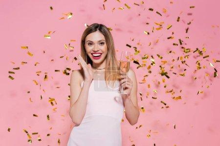 Jolie femme avec champagne regardant la caméra près de confettis dorés pendant la fête sur fond rose