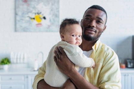 Photo pour Homme afro-américain embrassant bébé fille à la maison - image libre de droit