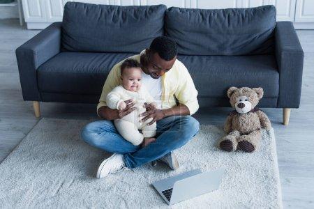 Photo pour Homme afro-américain tenant bébé tout en étant assis sur le sol près d'un ordinateur portable et ours en peluche - image libre de droit