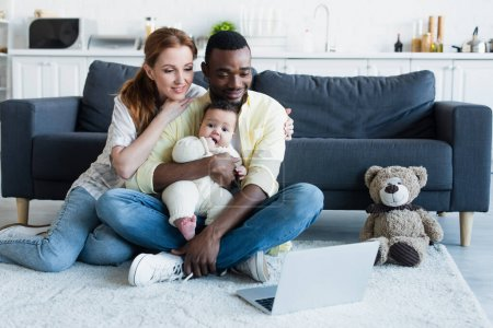 joyful multiethnic family watching movie on laptop while sitting on floor