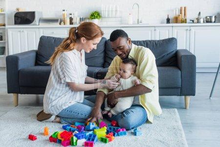 Multiethnisches Paar sitzt mit Baby auf dem Boden in der Nähe bunter Bauklötze