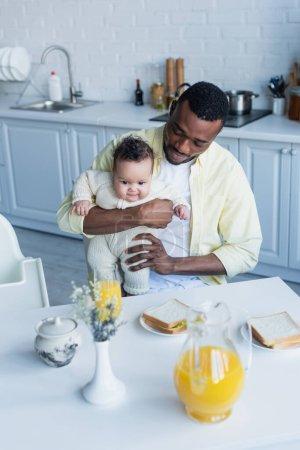Photo pour Homme afro-américain assis avec fille bébé près de la table avec petit déjeuner - image libre de droit