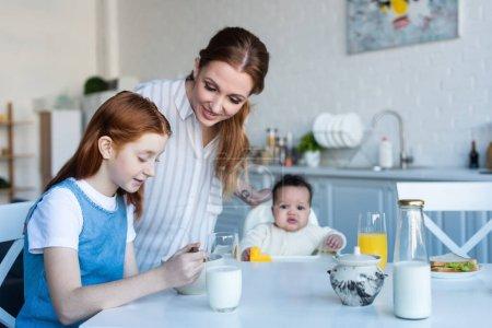 Photo pour Femme souriant près de filles interracial pendant le petit déjeuner dans la cuisine - image libre de droit