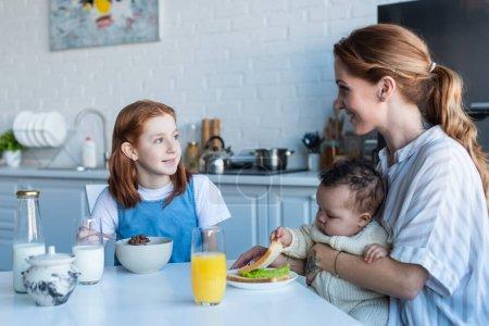 happy woman having breakfast with multiethnic daughters in kitchen