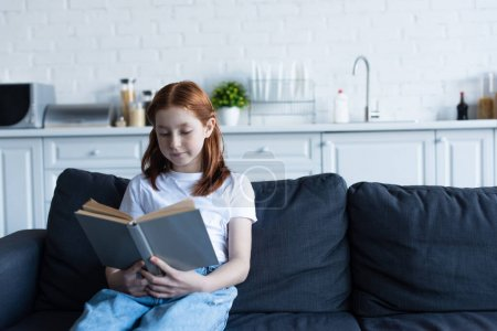 Photo for Preteen girl reading book on sofa in kitchen - Royalty Free Image