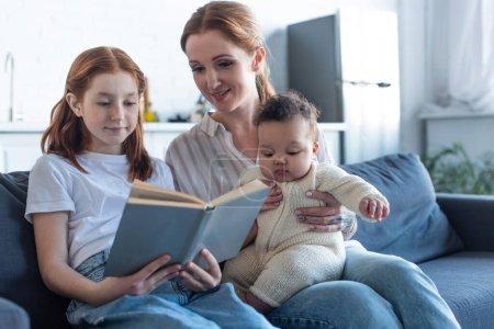 Photo pour Souriant fille lecture livre près de mère et bébé afro-américaine soeur - image libre de droit