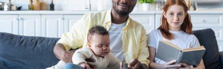 Photo pour Fille tenant le livre près du père afro-américain et de la sœur infantile sur le canapé à la maison, bannière - image libre de droit