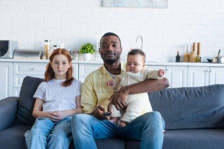 Photo pour Heureux afro-américain homme tenant bébé tout en regardant la télévision près de fille préadolescente - image libre de droit